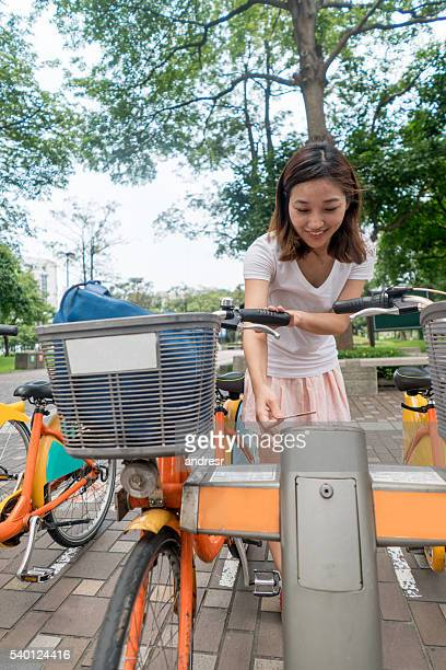 Asian woman renting a bicycle