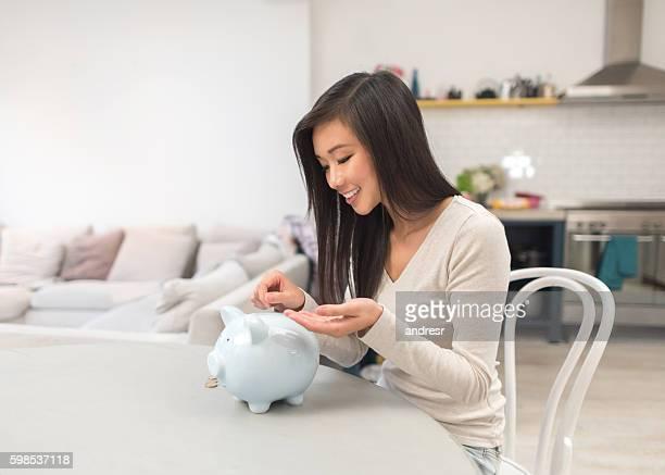 Asian woman saving money in a piggybank