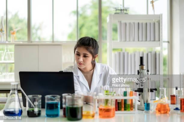 asian woman scientist student checking results on her laptop in a laboratory lab. - wissenschaftlerin stock-fotos und bilder