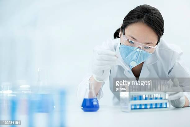 Asiatische Frau Wissenschaftler arbeiten mit Chemikalien die Schutz- und Arbeitskleidung