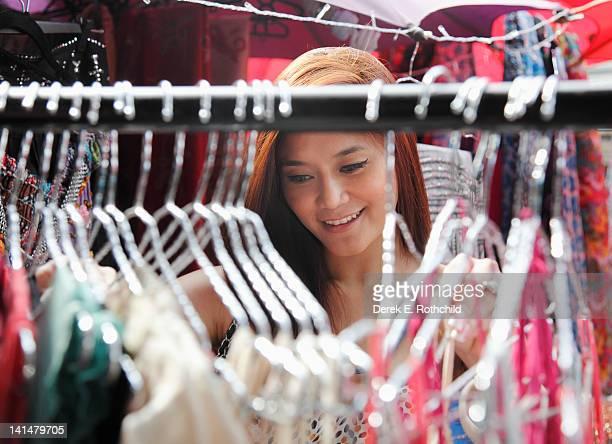 asian woman seen through clothes on rack - nur erwachsene stock-fotos und bilder