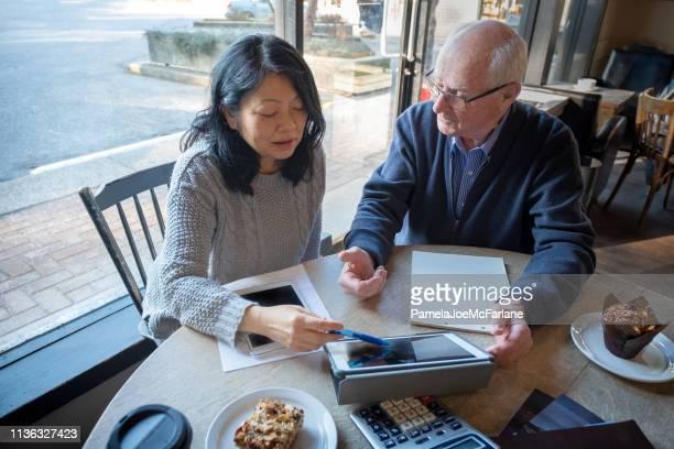 donna asiatica, uomo anziano che rivede le informazioni finanziarie sul tablet digitale - fondo pensionistico personale foto e immagini stock