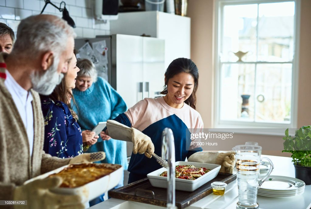 Asian woman serving home made food in busy family kitchen and smiling : Stock Photo