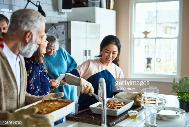 Asian woman serving home made food in busy family kitchen and smiling