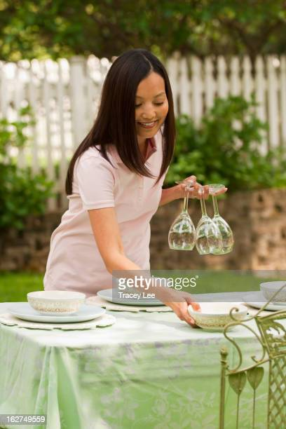 Asian woman setting table outdoors