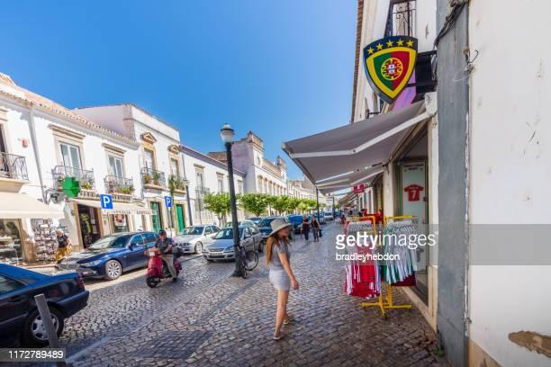 asian woman shopping along rua da liberdade in tavira, portugal - rua stock pictures, royalty-free photos & images
