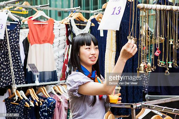 Asian woman shopping at marketstall.