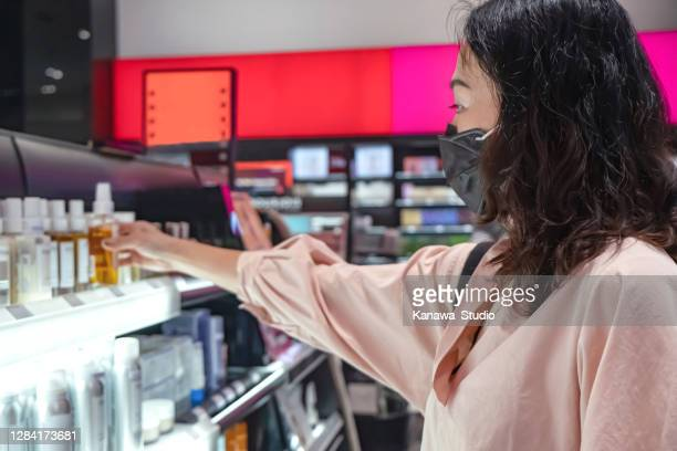 asian woman shopping hair care product in department store - face mask beauty product stock pictures, royalty-free photos & images