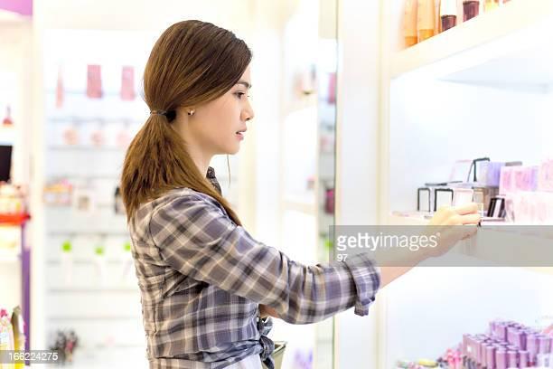 アジアの女性のショッピングには、化粧品を保管します。