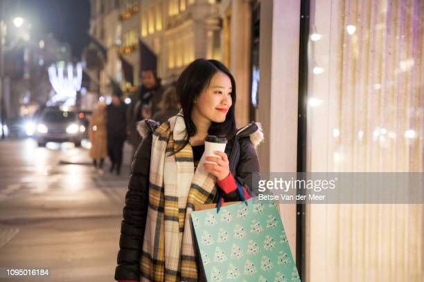 asian woman shopping, looking in shop window while walking. - 欲望 ストックフォトと画像