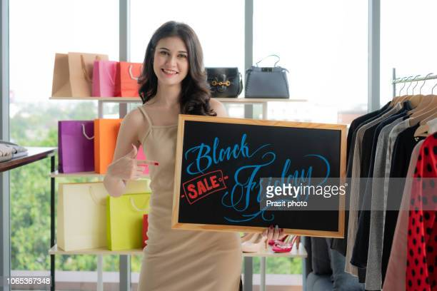 asian woman showing black friday sale banner in retail shop. - black friday stock photos and pictures