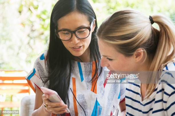 Asian woman shows photos on phone to her friend.