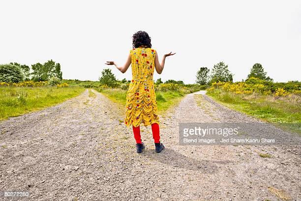Asian woman shrugging at split in road