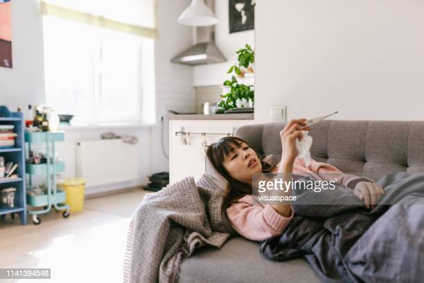 アジアの女性病気自宅で測定温度 - 温度 ストックフォトと画像