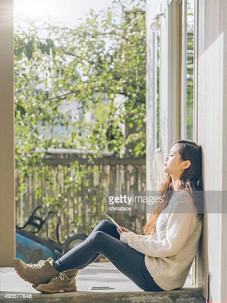 Asiatische Frau Sitzen im Balkon mit holding tablet pc