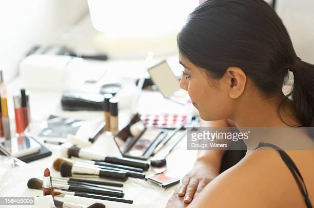 Asian woman sitting at desk looking at make up.