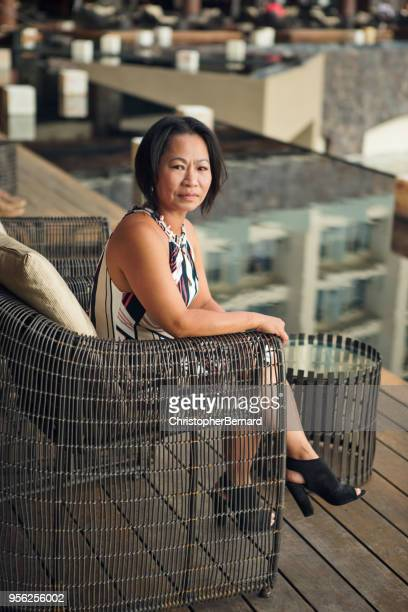 asian woman sitting at patio - pretty vietnamese women stock photos and pictures