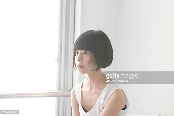 Asian woman sitting besides windowsill