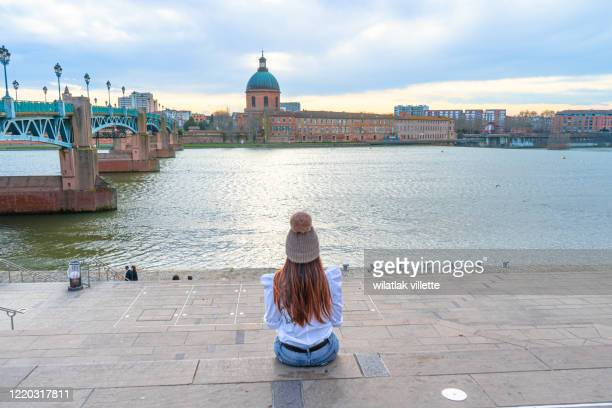 asian woman sitting garonne river and dome de la grave in toulouse, france - toulouse stock pictures, royalty-free photos & images