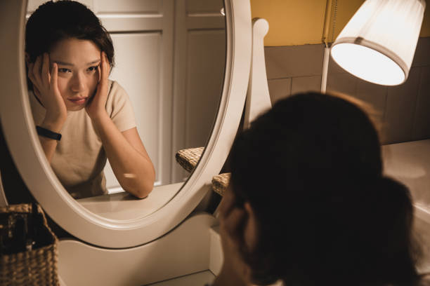 asian woman sitting in front of the dressing table feeling depressed - woman anxiety stock pictures, royalty-free photos & images