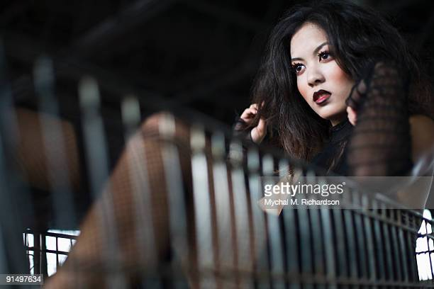 Asian woman sitting in shopping cart