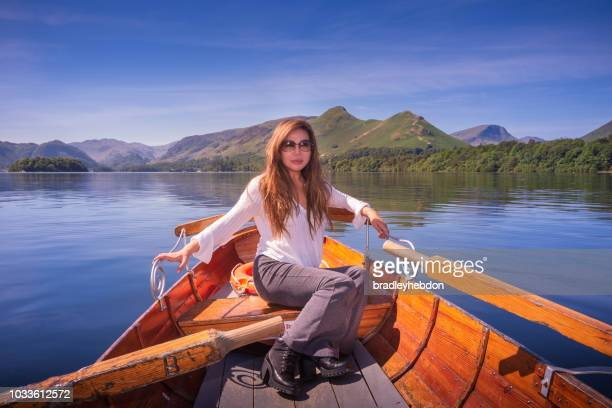 Asian woman sitting in wooden boat on Lake Derwentwater near Keswick, England
