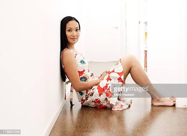 Asian Woman Sitting on Hallway Floor