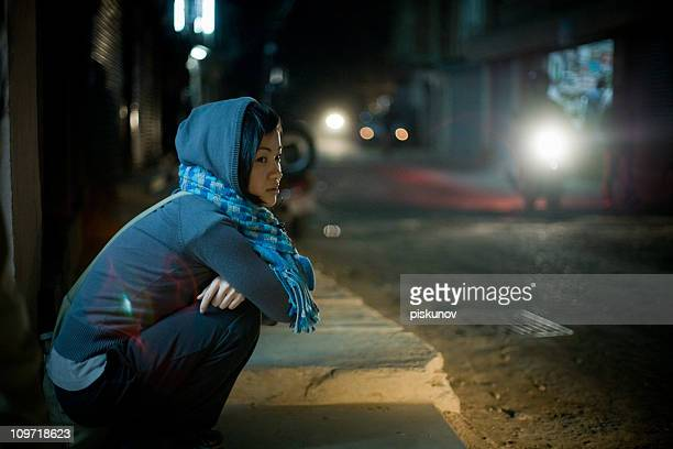 Asian woman sitting on street at night