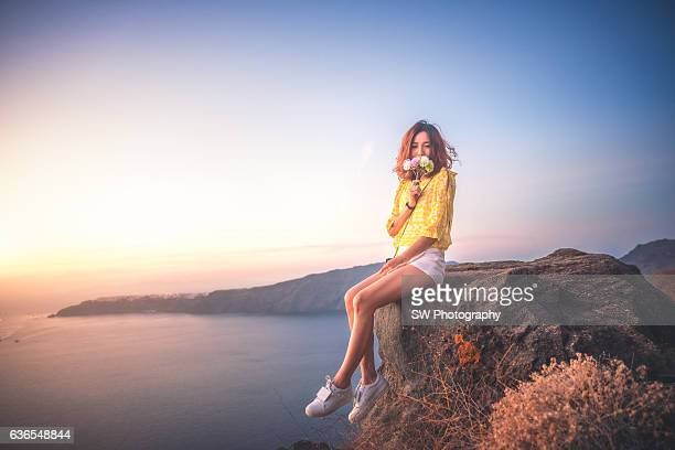 Asian woman sitting on the cliff