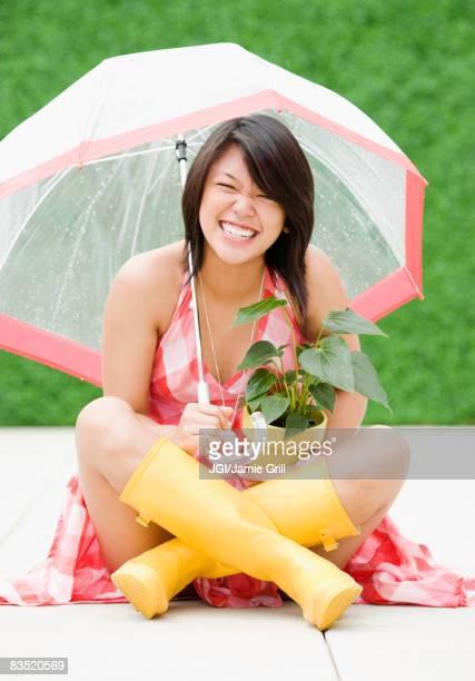 Asian woman sitting underneath umbrella in rain