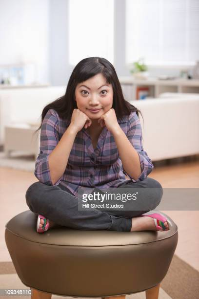 Asian woman sitting with head in hands