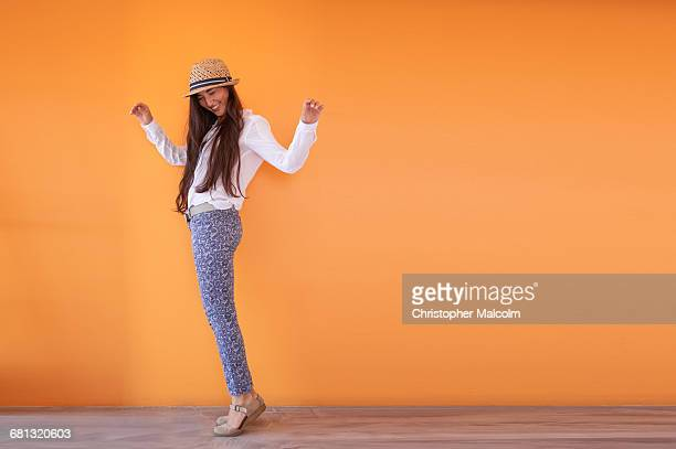 asian woman smiling in front of orange wall - white pants stock pictures, royalty-free photos & images