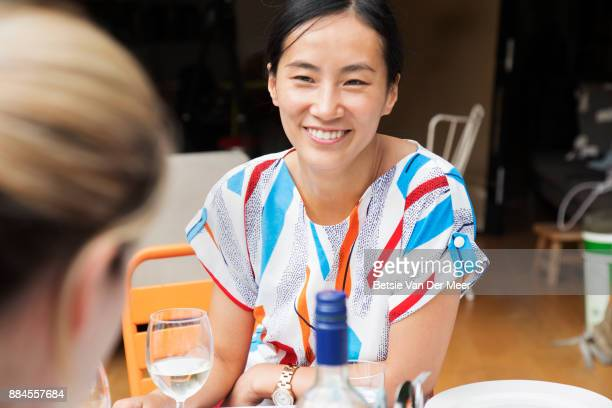 Asian woman smiling, talking to friend at garden party.