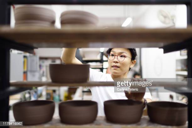 asian woman stacking clay dishes on shelves - singapore stock pictures, royalty-free photos & images