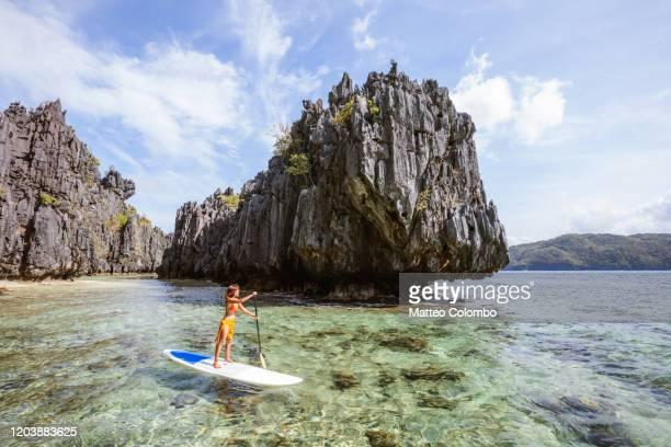 asian woman stand up paddling, el nido, philippines - paesaggio marino foto e immagini stock
