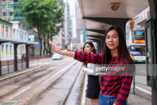 asian woman standing and waiting for transport at a street in north point, hong kong - wanchai stock photos and pictures