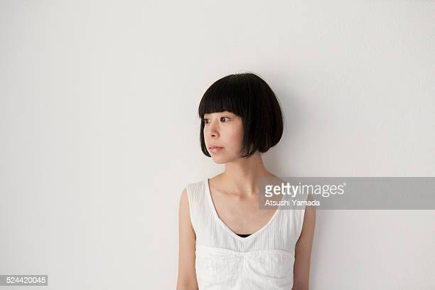 Asian woman standing besides the wall