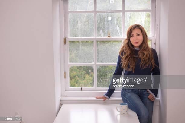 Asian woman standing near apartment window