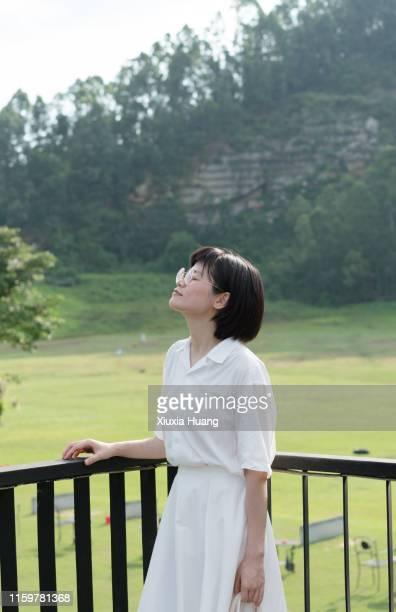 asian woman standing on balcony railing - 白い服 ストックフォトと画像