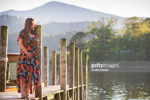 Asian woman standing on pier overlooking Lake Derwentwater in Keswick, England
