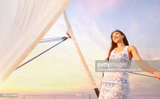 Asian woman standing on sailboat