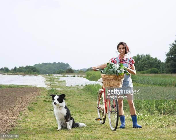 Asian woman standing with dog and bicycle on farm.