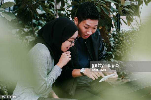 asian woman suprised looking at phone - rifka hayati stock pictures, royalty-free photos & images