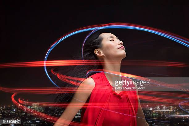 asian woman surrounded by lightbeams over city. - fantasy stock pictures, royalty-free photos & images