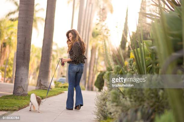 Asian woman takes her senior Shih Tzu dog for a walk