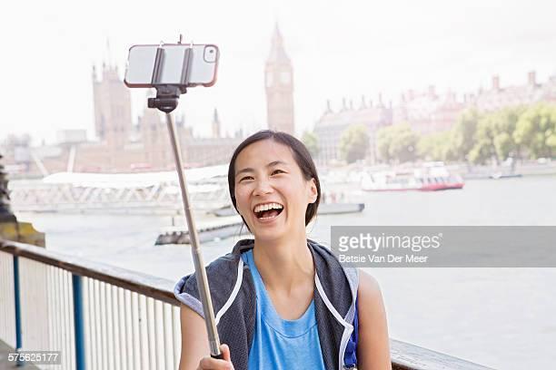 Asian woman takes Selfie near Big Ben and Thames