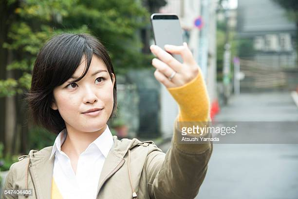 Asian woman taking photograph of herself with mobi