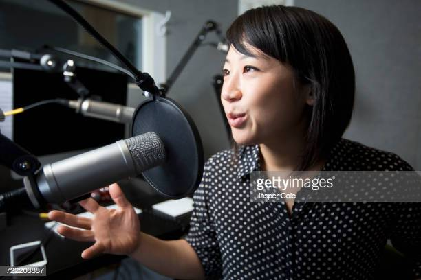 asian woman talking into microphone - podcast stock-fotos und bilder