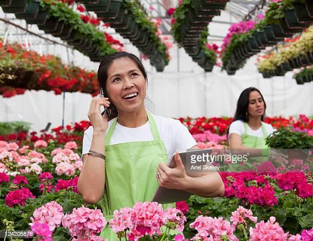 Asiatische Frau reden auf Handy in Gartenbau-Betrieb