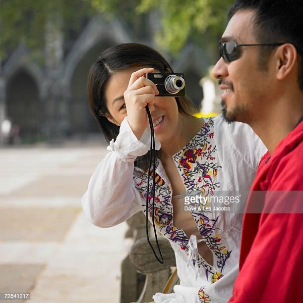 asian woman talking photograph of asian man outdoors - サングラス ストックフォトと画像